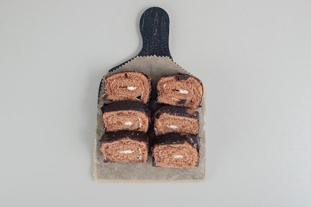 Rotolo di cioccolato dolce a fette su una tavola di legno.