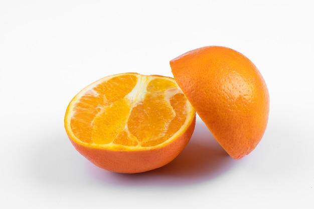 Sliced sweet orange fruit placed on a white background .