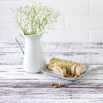 꽃으로 장식된 흰색 나무 책상에 피스타치오를 곁들인 얇게 썬 타히니 할바.