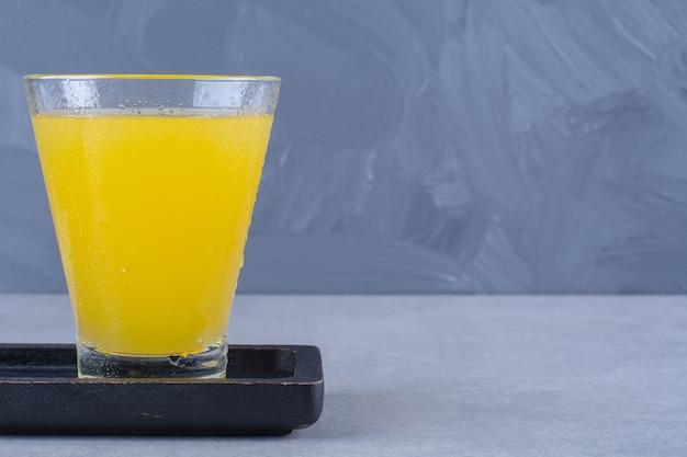 대리석 테이블에 있는 나무 접시에 있는 오렌지 주스 한 잔 옆에 얇게 썬 귤.