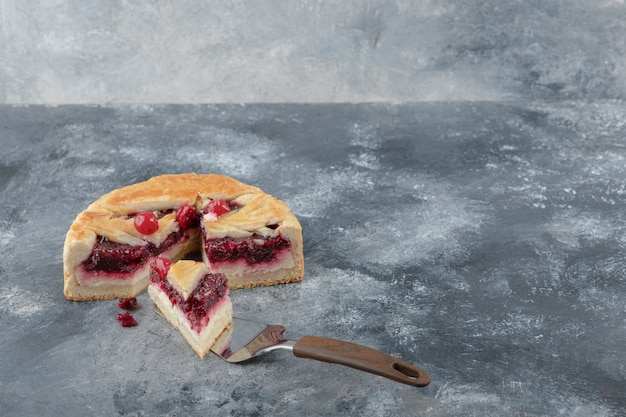 Sliced tasty cheesecake with berries placed on marble background.