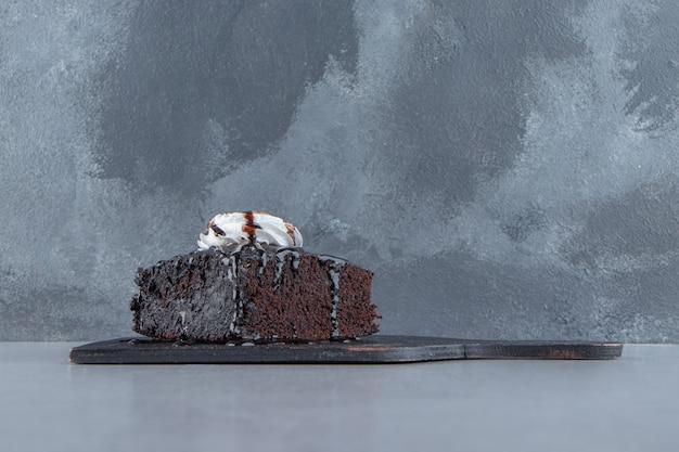 Fette di gustoso brownie al cioccolato con crema sul tagliere. foto di alta qualità