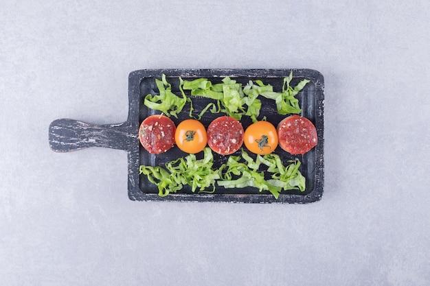 Gustose salsicce affettate con ketchup e pomodori su tavola nera.