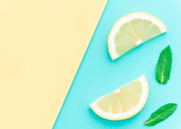 Sliced tasty sour lemon and green leaves