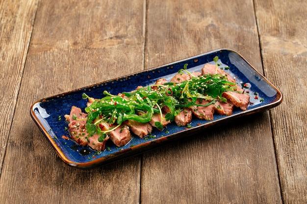 木製の背景に海苔チュカとスライスしたたたきロースト鴨胸肉