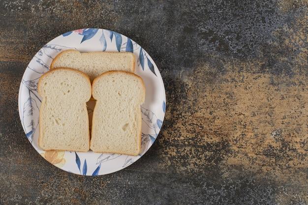 Нарезанный тостовый хлеб на красочной тарелке.
