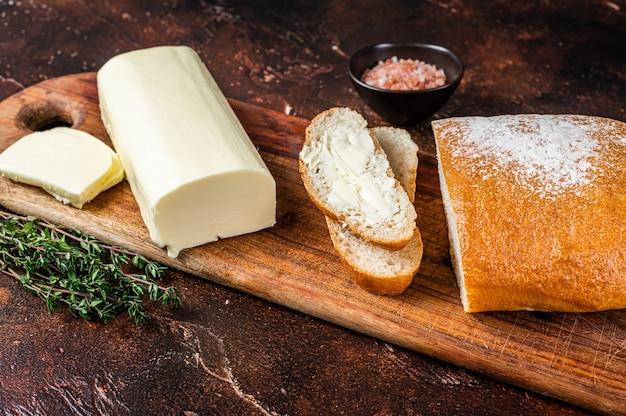 На деревянной разделочной доске нарезанный тостовый хлеб с маслом. темный фон. вид сверху.