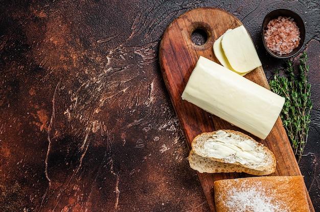 나무 커팅 보드에 버터와 함께 슬라이스 토스트 빵. 어두운 테이블. 평면도. 공간을 복사하십시오.