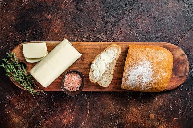 나무 커팅 보드에 버터와 함께 슬라이스 토스트 빵. 어두운 테이블. 평면도.