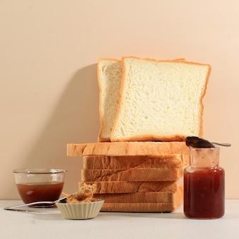 木製の背景に朝食用のスライスしたトーストローフ白パン、卵とミルクを添えて。ベーカリーコンセプト画像
