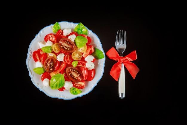 クリスマスディナーにトマトとモッツァレラチーズのスライスサラダとフォーク。ベジタリアン料理。