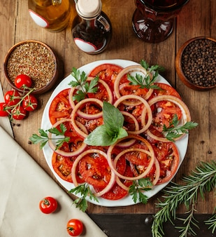 Sliced tomato and onion with herbs