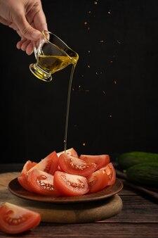 Нарезанный томатный овощ подается на тарелке с ручной заливкой оливкового масла и специй, падающих на стол