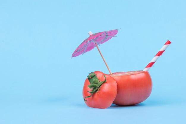 Нарезанный помидор с зонтиком для коктейля и соломинкой на синем фоне.