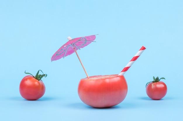 Нарезанный помидор с зонтиком и трубочкой для коктейля на фоне целых помидоров на синем.