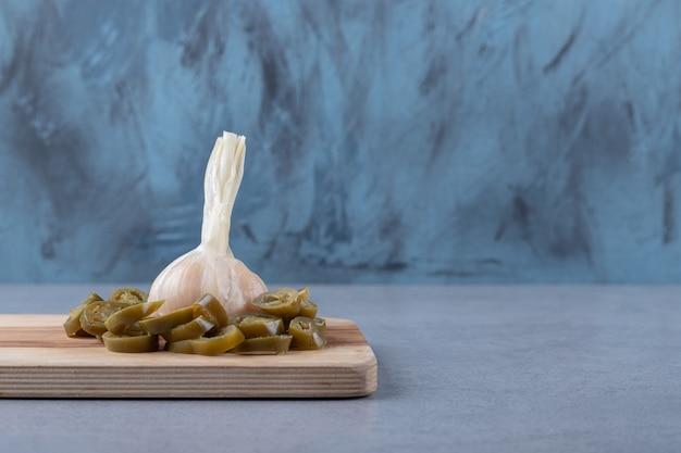 Pomodoro affettato con aglio sul tagliere, sullo sfondo di marmo.