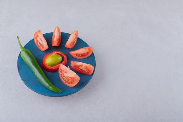Нарезанные помидоры и перец чили на тарелке, на мраморе.