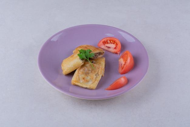어두운 표면에 접시에 고기와 토마토와 팬케이크 슬라이스