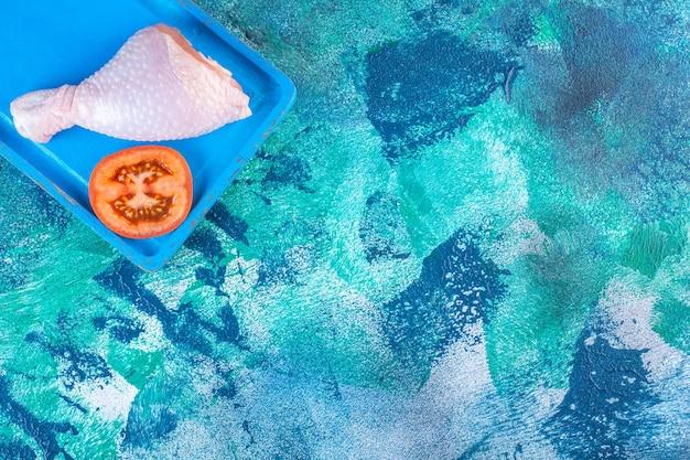 Нарезанные помидоры и сырая куриная голень на деревянной тарелке