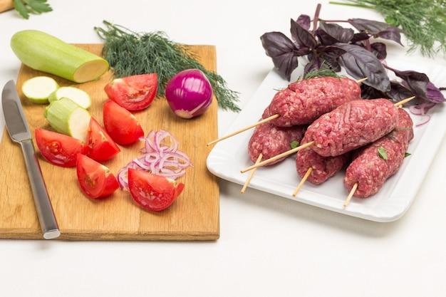 まな板の上でスライスしたトマトとズッキーニ。木製の串に刺した生のひき肉。ケバブ料理。白色の背景。