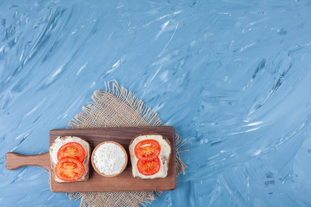 Sliced tomatoes on cheese bread and a bowl of flour on cutting board on burlap napkin on blue.