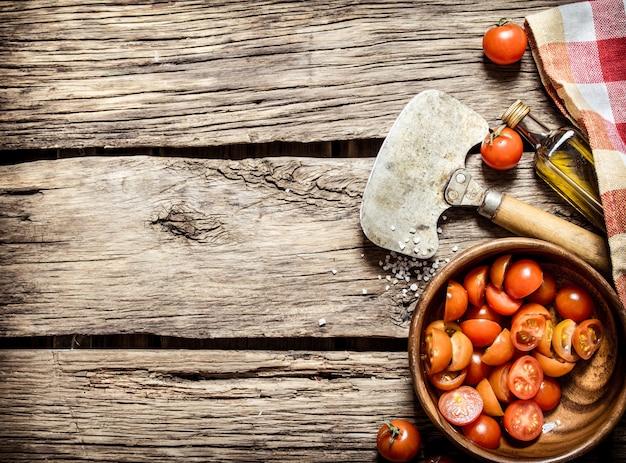 Нарезанные помидоры в чашке с оливковым маслом на деревянном столе.