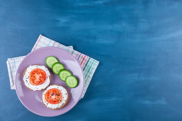 Нарезанные помидоры на сырном хлебе рядом с огурцом на тарелке, на кухонном полотенце, на синем.