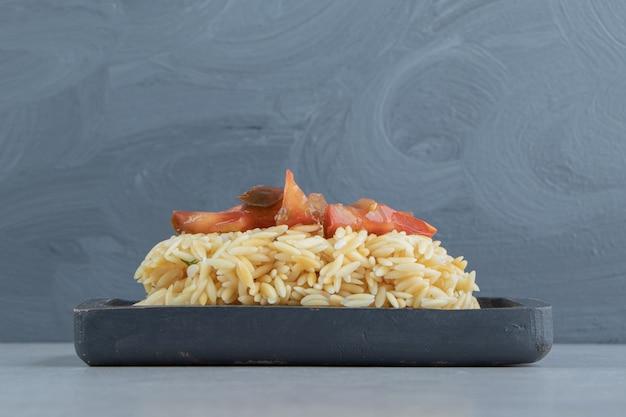 Нарезанные помидоры на деревянной тарелке с рисом, на мраморе.