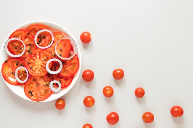 Sliced tomatoes and onions in plate on white background