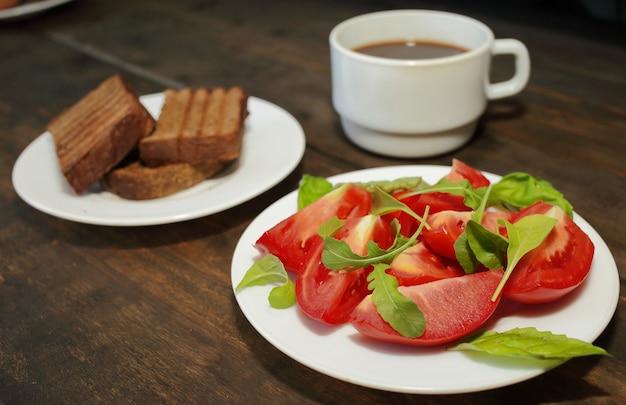 토스트와 커피 한잔과 함께 하얀 접시에 샐러드와 토마토 슬라이스