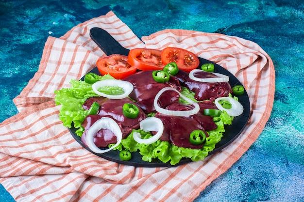На разделочной доске на кухонном полотенце нарезать различные овощи и куриную печень.