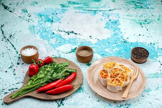 スライスした野菜は、明るい青色の机の上に緑と赤のスパイシーな唐辛子と一緒においしいフィリングで生地をロールバックします