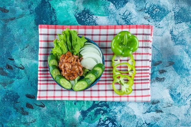 青いテーブルの上で、タオルの上の木の皿に野菜とベイクドビーンズをスライスしました。