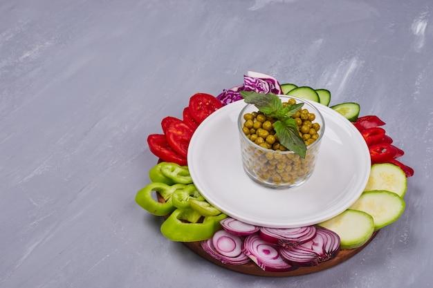 青いテーブルの上の白い皿に野菜とハーブをスライスしました。