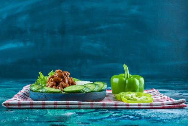 Sliced vegetables and baked beans on a wooden plate on a towel , on the blue background.