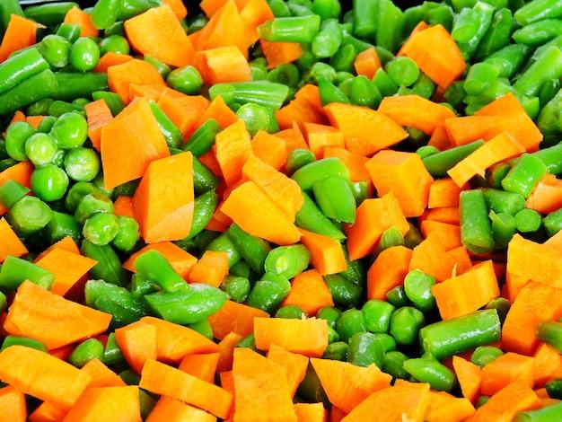 Sliced vegetables before baking on the pan for baking. carrots, green peas, green beans.