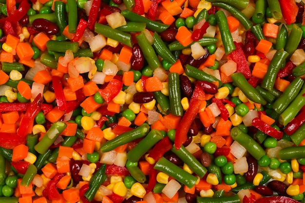 Sliced vegetables, corn, beans, peas, carrots, sweet peppers background.