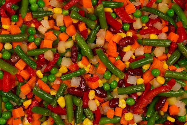 Нарезанные овощи, кукуруза, фасоль, горох, морковь, сладкий перец фон.