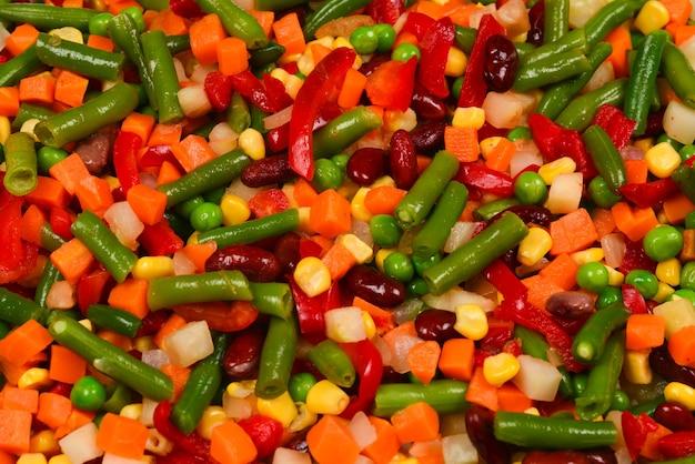 スライスした野菜、トウモロコシ、豆、エンドウ豆、ニンジン、ピーマンの背景。