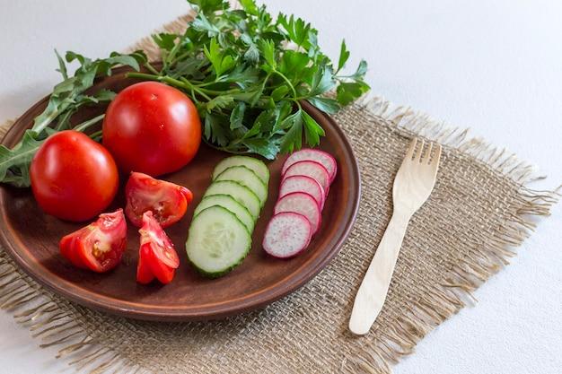 木のフォークで皿にスライスした野菜