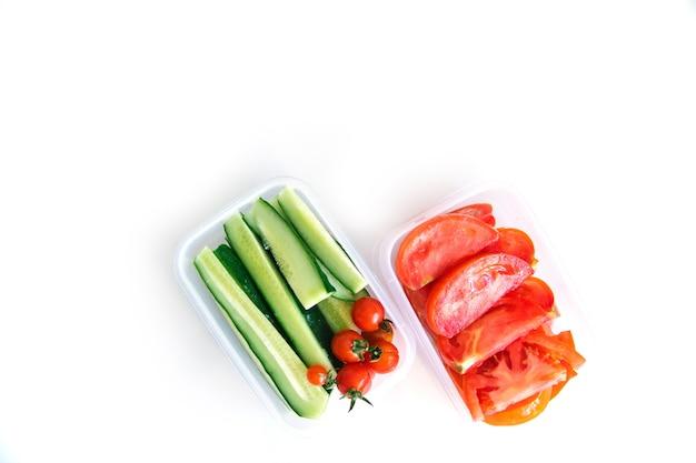 Нарезанные овощи в пластиковых контейнерах на белом фоне. огурцы и помидоры в контейнерах. здоровое и правильное питание. упакованный ланч для работы или путешествий.