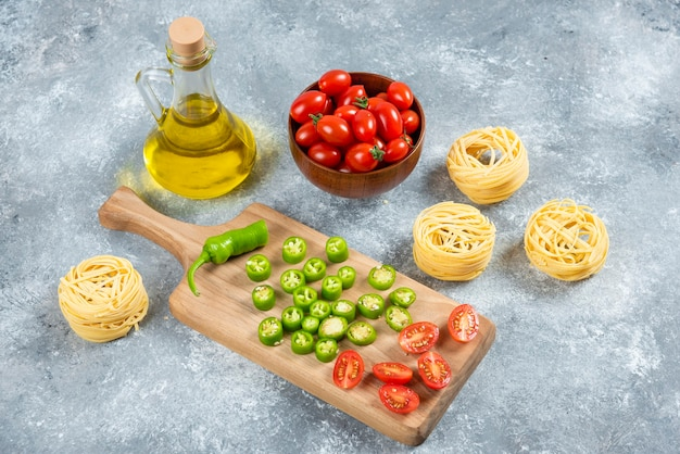Sliced vegetables, olive oil and pasta nests on marble background.