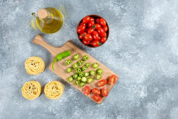 Sliced vegetables, olive oil and pasta nests on marble background.
