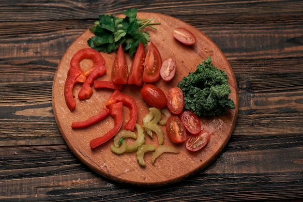 Нарезанные овощи на круглой деревянной доске