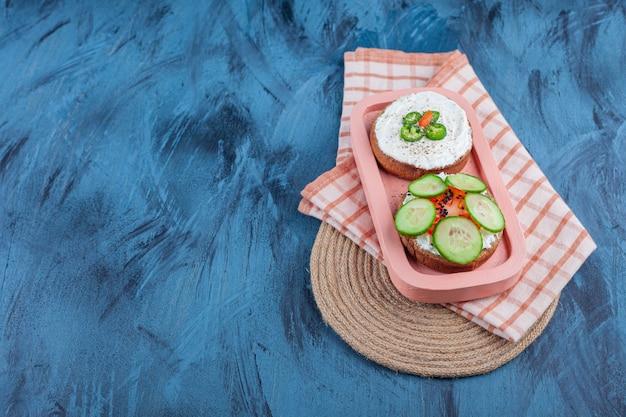 青のトリベットのタオルの上のボードのチーズパンにスライスした野菜。