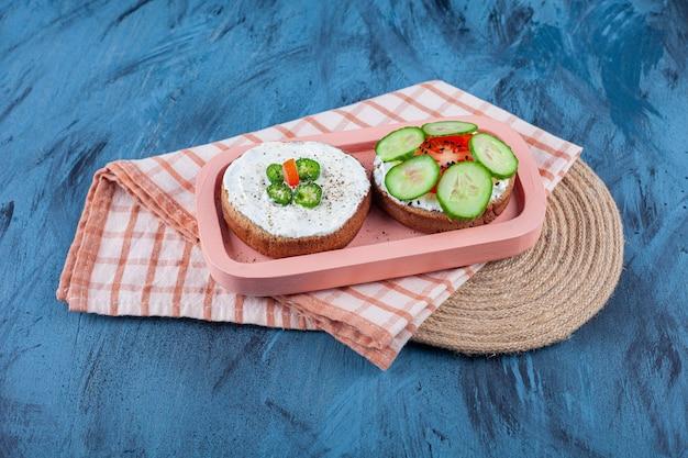 Нарезанные овощи на сырном хлебе на доске на полотенце на подставке, на синем столе.