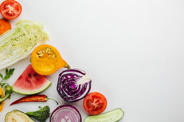 Sliced veggies on white background with copy space