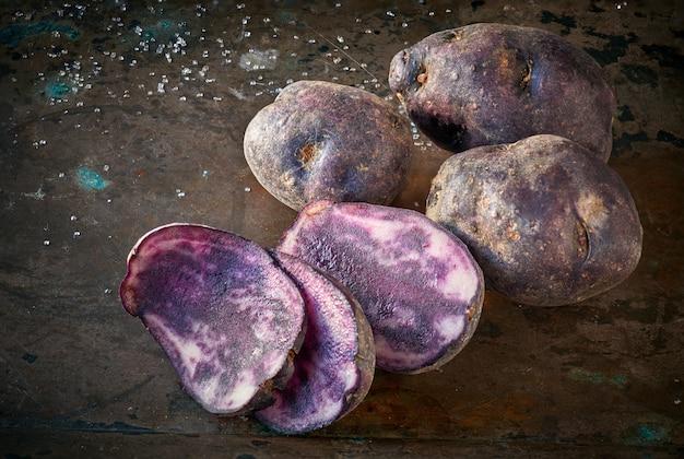 Нарезанный картофель vitelotte, три ломтика и три целых картофеля на темном