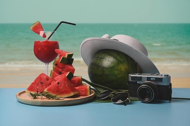 スライスしたスイカとスイカのスムージーをテーブルに、美しい夏のビーチを背景に。