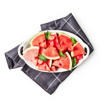 Нарезанные ягоды арбуза, свежие фрукты на тарелке с салфеткой. группа объектов, изолированных на белом фоне включен путь клиппирования. вид сверху, плоская планировка